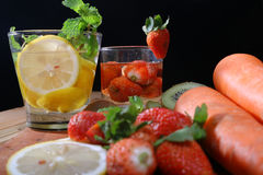 Drink from the juice of fruits such as melons, strawberries, kiwi, carrots, with a black background Stock Photography