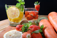 Drink from the juice of fruits such as melons, strawberries, kiwi, carrots, with a black background Stock Image