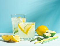 A drink of lemon and lime lemonade in transparent glasses ablue background bright sunlight. Summer cocktail or mojito. A drink of lemon and lime lemonade in royalty free stock image