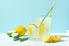 A drink of lemon and lime lemonade in transparent glasses a blue background bright sunlight. Summer cocktail or mojito. A drink of lemon and lime lemonade in stock photography