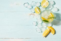 A drink of lemon and lime lemonade in transparent glasses blue background bright sunlight. Summer cocktail or mojito. A drink of lemon and lime lemonade in stock photos