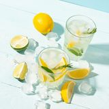 A drink of lemon and lime lemonade in transparent glasses a blue background bright sunlight. Summer cocktail or mojito. A drink of lemon and lime lemonade in stock photo