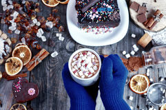 Drink with marshmallow in his hands over a table with sweets Royalty Free Stock Image