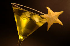 Drink in martini glass with star fruit 1. Yellow drink in martini glass with star fruit stock image