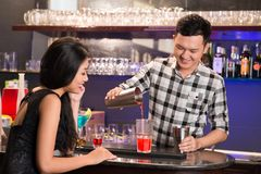 Drink mixing. Asian barman mixing a drink to a girl royalty free stock photography