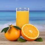 Drink och apelsiner för orange fruktsaft på stranden och havet Royaltyfri Bild