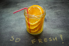 Drink with orange in a jar. Refreshing drink with orange in a jar with a straw Royalty Free Stock Images