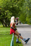 Drink pause. Adult woman on rollerskates stopping for a drink Royalty Free Stock Image