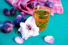 Drink, plums and flowers. On the board Stock Photo