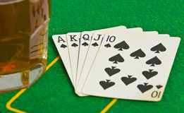 Drink on poker table with cards Royalty Free Stock Images