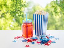 Drink and popcorn with candies on independence day. American independence day, celebration and holidays concept - close up of juice glass or mason jar, popcorn royalty free stock photography