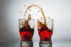 A drink pouring from a glass into a glass. напиток который переливается из стакана в стакан Stock Photography
