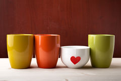Drink is prepared with love. Cups of different colors stand in a row on white heart Stock Image