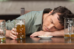 Drink responsibly. Portrait of drunk men sitting at the pub with. Drink responsibly. Portrait of drunk man sitting at the pub with his eyes closed Royalty Free Stock Photography