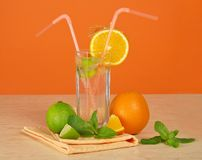 Drink, ripe orange, juicy lime and napkin Royalty Free Stock Image