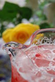 Drink and Rose. Strawberry Lemonade and a yellow rose in background Royalty Free Stock Photography