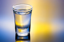 Drink shot. Glass with reflection in yellow and blue Stock Photography
