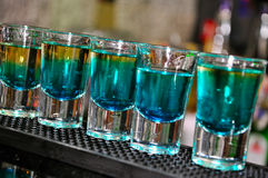 Drink in shot glasses standing on the club counter. Blue drink in shot glasses standing on the counter Royalty Free Stock Photos