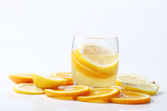 Drink and stack of citrus fruits slices. Oranges and lemons. Stock Photo