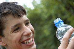 Drink of summer. Smiling teens with bottle of the water royalty free stock photo