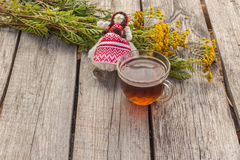 Drink from tansy and folk doll on wooden table Royalty Free Stock Image