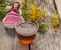 Drink from tansy and folk doll on wooden table Royalty Free Stock Photos
