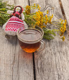 Drink from tansy and folk doll on wooden table Stock Photography
