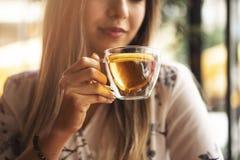 Drink Thee ontspannen comfortabele foto met vage achtergrond Vrouwelijke handen die mok hete Thee in ochtend houden Jonge vrouw h royalty-vrije stock foto's