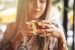 Drink Thee ontspannen comfortabele foto met vage achtergrond Vrouwelijke handen die mok hete Thee in ochtend houden Jonge vrouw h stock foto