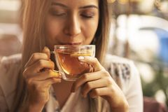 Drink Thee ontspannen comfortabele foto met vage achtergrond Vrouwelijke handen die mok hete Thee in ochtend houden Jonge vrouw h royalty-vrije stock afbeelding