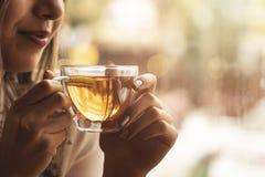 Drink Thee ontspannen comfortabele foto met vage achtergrond Vrouwelijke handen die mok hete Thee in ochtend houden Jonge vrouw h stock afbeeldingen
