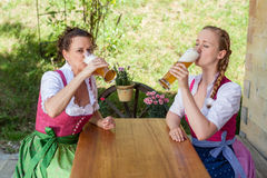 Drink Two women in Bavarian Dirndl with a beer. Two women in Bavarian Dirndl drinking beer on a mountain pasture in the beer garden royalty free stock photography