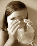Drink it up. Little girl drinking milk.  Sepia tone Stock Image
