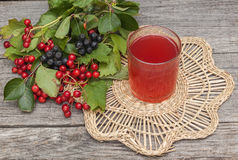 Drink of the viburnum and aronia on a wooden background Royalty Free Stock Image