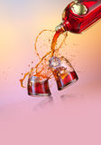 Drink. View of two glasses are being filled with splash on color back Royalty Free Stock Image