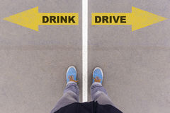 Drink vs drive text arrows on asphalt ground, feet and shoes on Stock Image