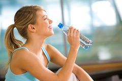 A drink of water. Profile of beautiful woman going to drink some water from plastic bottle after workout Stock Image