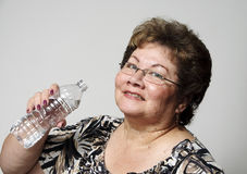 Drink water. An older hispanic woman smiles as she is about to drink from her water bottle Stock Photos