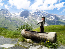 Drink water. Wooden well with drink water in alps mountains, beauty cloudy and sunny day Stock Photo