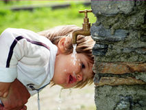 Drink water. Pretty little girl drinking from a water fountain Stock Image