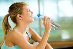 A drink of water. Profile of beautiful woman going to drink some water fron plastic bottle after workout stock images