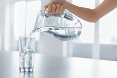 Drink water De Hand Gietend Water van de vrouw van Waterkruik in een Glas Royalty-vrije Stock Afbeelding