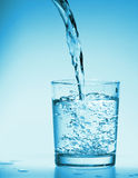 Drink Water poring into a  glass. On blue Royalty Free Stock Images