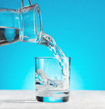 Water pouring into a glass on blue background Royalty Free Stock Images