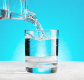 Water pouring into a glass on blue background Royalty Free Stock Image