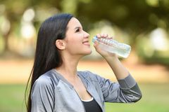 Drink water after sport. Beautiful young woman drink water after sport - outdoors training girl morning fitness exercises Royalty Free Stock Photos