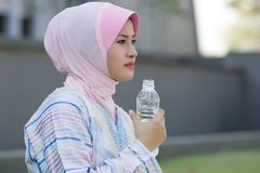 Drink water while staring ahead. Young muslim girl holding a bottle of mineral water while staring ahead Royalty Free Stock Photo