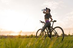 Drink water during workouts. sports. woman on bike sunset royalty free stock photo