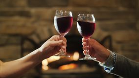 Drink wine near the fireplace. Two female hands clink glasses of red wine. Clinking glasses on the background of a burning fireplace stock video footage