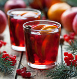 Drink on winter evening. Hot granberry orange pomegranate punch or mulled wine, sangria in a rustic wooden table Stock Images